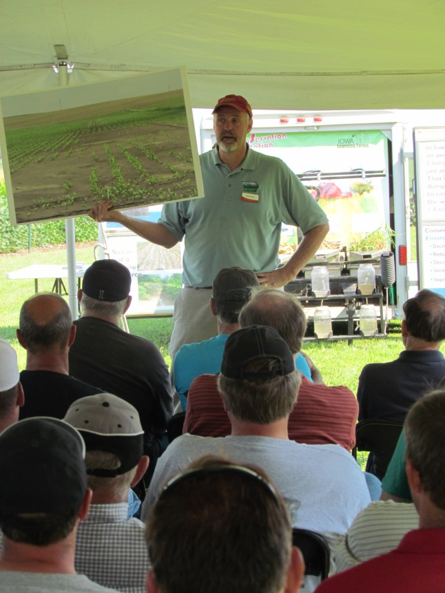 ISUEO field agronomist Joel De Jong shows field day attendees an image taken this May in the local area illustrating soil erosion and deposition.