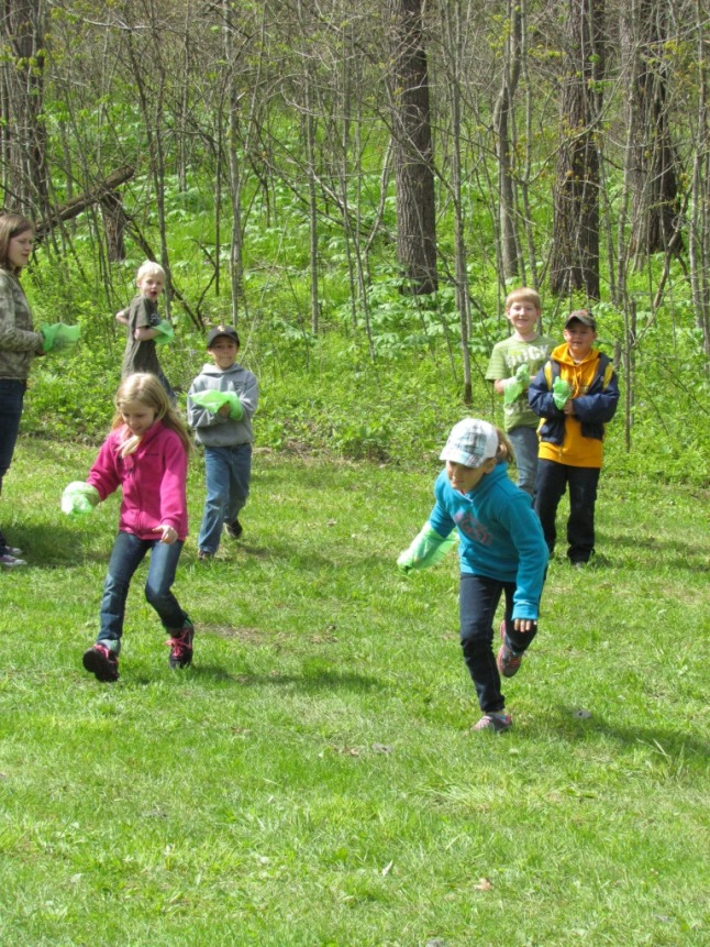 Intern Liz Gotzinger (left) leads students in the Great Poo Pickup Relay at an outdoor classroom event
