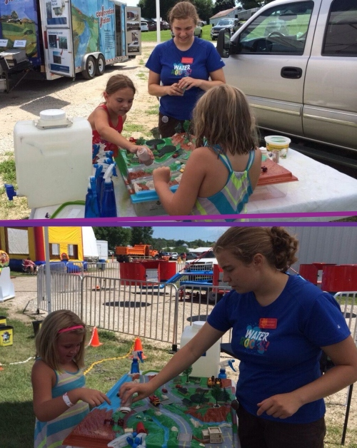 Megan Koppenhafer, fellow intern, adding loose soil to the watershed, with an eager repeat visitor (in stripes), at the Audubon County Fair.