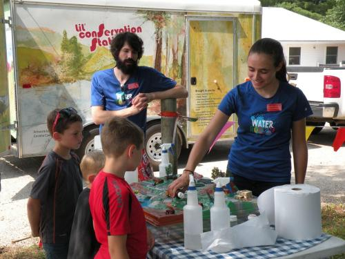 Jessica Rehmann adding oil to the landscape (Brian Stout looks on) at the Dallas Co. Fair.
