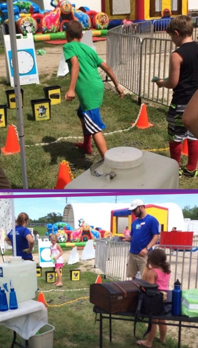 Kids trying their hand at the Poo Toss to win prizes from the treasure chest with intern Megan Koppenhafer and staffer Ben Schrag.